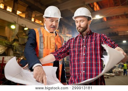 Aged and young builders or engineers discussing blueprint at working meeting in industrial plant