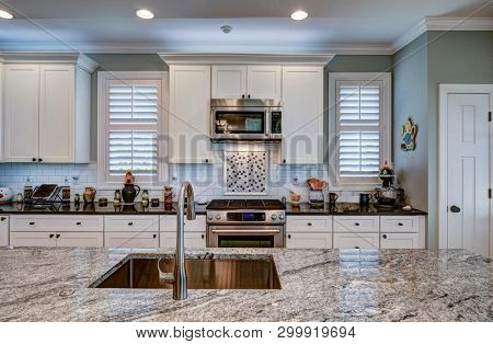 Luxury kitchen remodel with granite island in foreground.