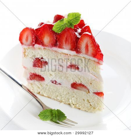 piece of cake on white plate with strawberries