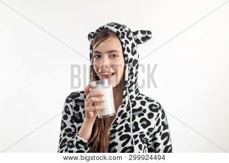 Maybe A Hot Bath And A Glass Of Milk. Young Pretty Woman In Spotted Cow Pajama Holding Glass Of Milk