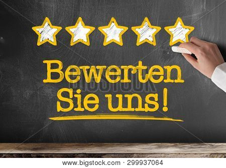 Text Bewerten Sie Uns, German For Rate Us Or Rate Our Service, Written On Blackboard With Five Golde