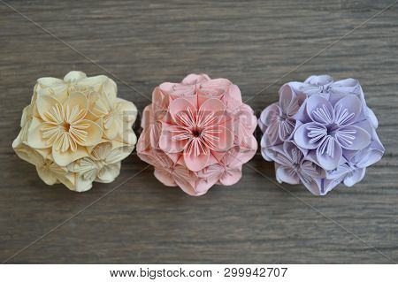 Yellow, Pink And Purple Origami Kusudama Flower On Wooden Background