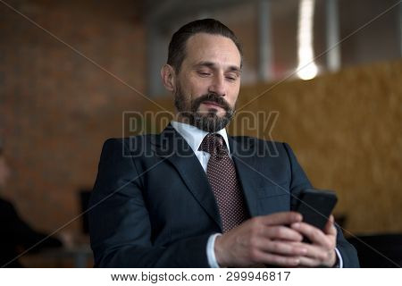 A Successfull Businessman Reading A Text Message On A Cellphone While Sitting In His Office.he Is Sm