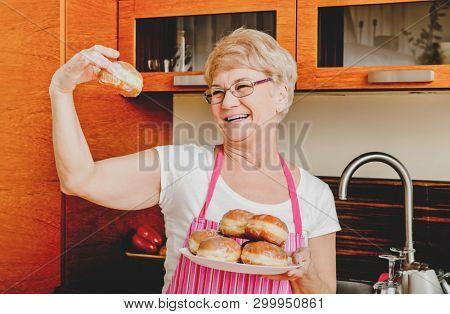 Smiling senior woman showing her homemade doughnut in kitchen.