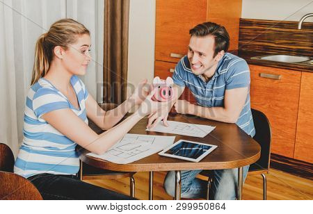 Couple checking their piggybank while planning renovation in home.