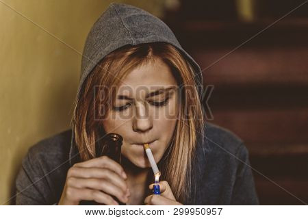Teenage girl is holding cigarette and bottle with beer. Illegal adolescent problem.