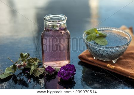 Close up of ingredients of popular Indian and Asian sherbat i.e. Gulab ka sherbat or rose milk on wooden surface which are soaked bail seeds and rose concentration or essence. poster