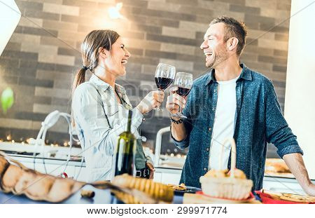 Young Couple In Love Drinking Red Wine At House Kitchen - Happy Millenial People At Home Enjoying Ap