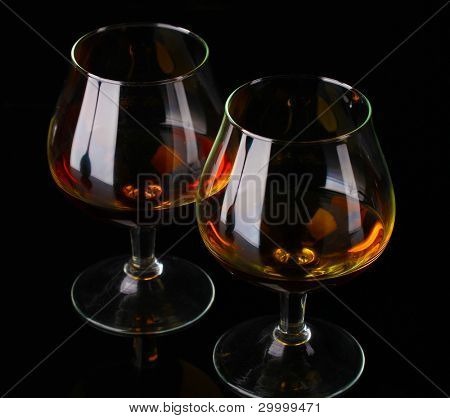 Two glasses of cognac on black background