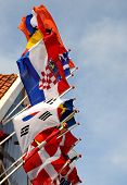 International flags blowing in the wind against sky poster