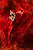 Beautiful woman in red waving silk dress as a fire flame as abstract background. Looking down. poster