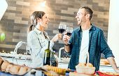 Young couple in love drinking red wine at house kitchen - Happy millenial people at home enjoying aperitif time cheering together at jubilee anniversary - Genuine youth concept on bright indoor filter poster