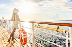 Luxury cruise ship travel elegant tourist woman watching sunset on balcony deck of Europe mediterranean cruising destination. Summer vacation cruiseship sailing away on holiday.