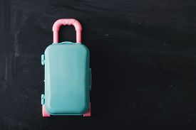 Color Suitcase On A Dark Background. Travel Concept.