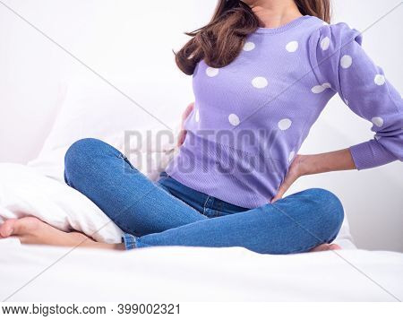 The Girl Is Sitting On The Bed In The Room Suffering From Back Pain. Spine Pain Health Care And Prob