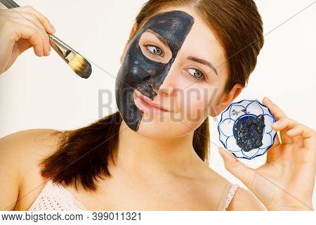 Female Applying Black Mud Mask To Face