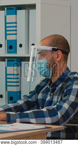 Handicapped Businessman With Visor And Protection Mask Working In New Normal Business Office. Man Di