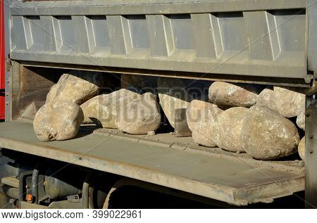 Moving Granite River Boulders From The Body Of A Truck. Open Sidewalls, Stones Are Rolled On The Law