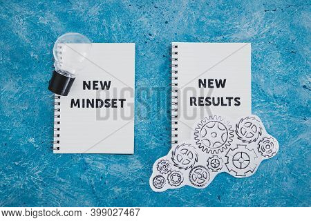 Law Of Attraction, Notepad With New Mindset New Results Text With Light Bulb And Gearwheel Mechanism