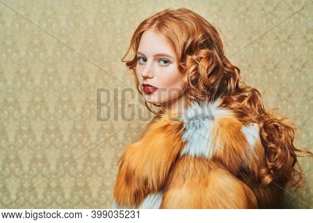 Beautiful young woman with long red hair poses in a luxurious fox fur coat on a golden vintage background. Winter beauty fashion. Fur coat style.