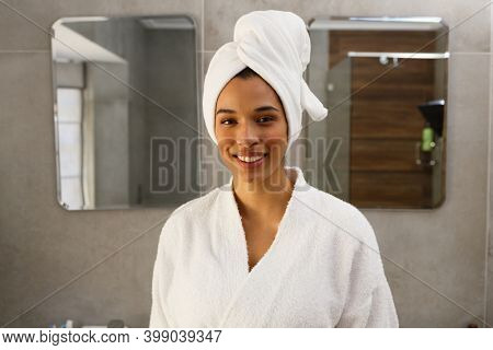 Portrait of smiling mixed race woman wearing bathrobe and towel on head in bathroom. self isolation at home during covid 19 coronavirus pandemic.