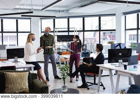 Diverse business people wearing face masks brainstorming in office. protection business office workplace during covid 19 coronavirus pandemic.
