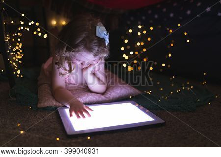 Caucasian girl lying in bedroom using digital tablet in the evening. enjoying quality time at home during coronavirus covid 19 pandemic lockdown.