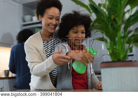 Mixed race woman and daughter watering plants in kitchen. self isolation quality family time at home together during coronavirus covid 19 pandemic.