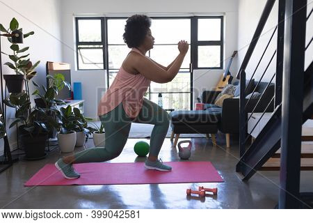 African american woman standing on exercise mat working out. self isolation fitness at home during coronavirus covid 19 pandemic.