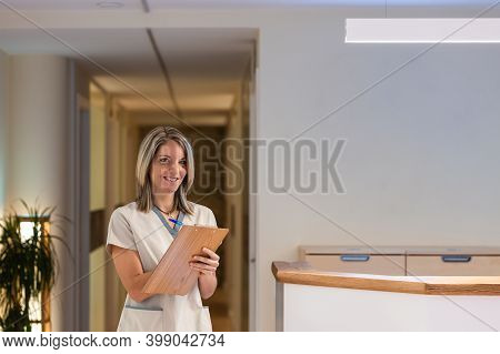 Female Receptionist Holding Folder With Documents In Hospital