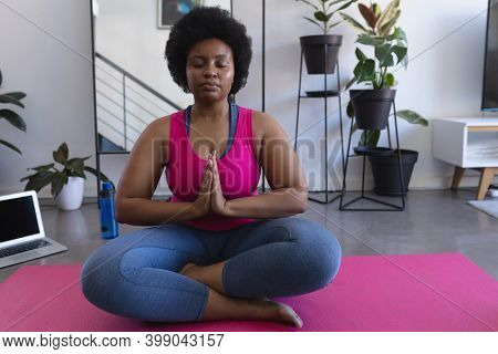 African american woman meditating sitting on mat wearing sports clothes. laptop in the background. self isolation fitness wellbeing technology at home during coronavirus covid 19 pandemic.