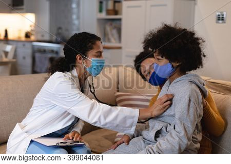 Mixed race girl wearing face mask being examined by mixed race female doctor sitting on couch. self isolation at home together during coronavirus covid 19 pandemic.