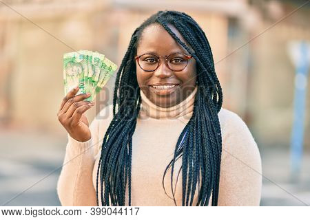 Young african american woman smiling happy holding south africa rands banknotes at the city.