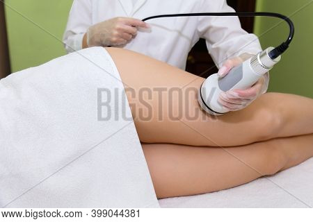 The Beautician Holds The Handpiece In His Hand And Guides The Client Along The Thigh And Buttocks. R
