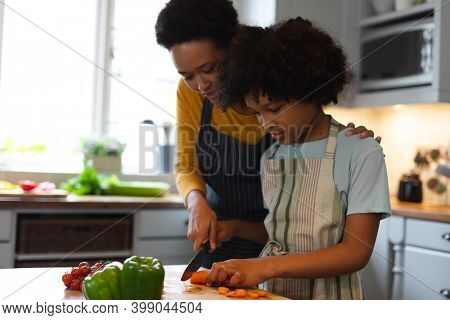 Mixed race woman and daughter preparing food in kitchen. self isolation quality family time at home together during coronavirus covid 19 pandemic.