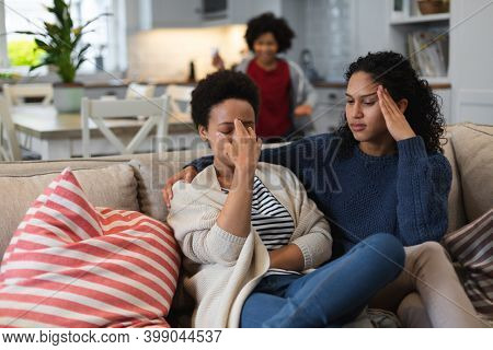 Upset mixed race lesbian sitting on couch. daughte rin the background. self isolation quality family time at home together during coronavirus covid 19 pandemic.