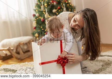 Beautiful Young Mother And Baby Boy Having Fun At Home On Christmas Day, Sitting By Nicely Decorated