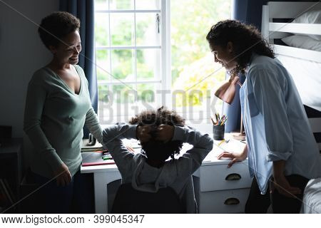 Mixed race lesbian couple talking with daighter sitting at desk. self isolation quality family time at home together during coronavirus covid 19 pandemic.