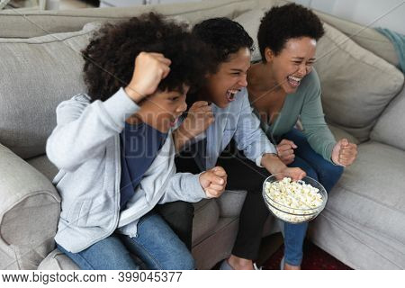 Mixed race lesbian couple and daughter sitting on couch watching tv and eating popcorn. cheering together. self isolation quality family time at home together during coronavirus covid 19 pandemic.