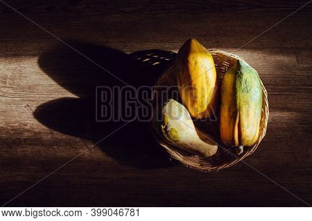 Papaya In A Wicker Basket On A Wooden Table, Light And Shadow Of Sunshine, Copy Space.