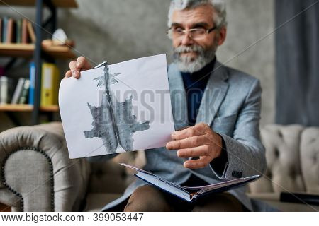Mature Psychologist Holding Picture With Ink Stain, Rorschach Inkblot During Therapy Session. Soldie