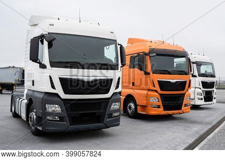 Trucks Stand In A Row At A Truck Stop. Close-up. Cargo Semi-trailers For Delivery And Loading Of Car