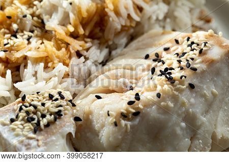 Steamed Cod Fillet With Rice. Cod With Rice Sprinkled With Sesame Seeds On A White Plate. Appetizing