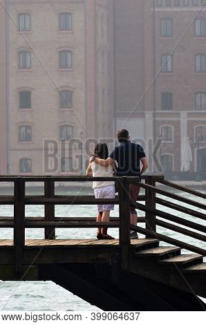 Rear View Of Mature Couple In Love On A Bridge Over Canal In Venice.  Looking At Venice Facade. Ital