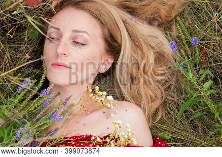 The Girl Lies On The Grass And Flowers In The Field. Portrait Of A Girl With Wildflowers. Portrait I
