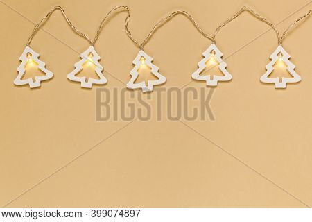 Christmas Glowing Garlands In The Form Of Light Bulbs On A Beige Background.gift Envelope With A Pho