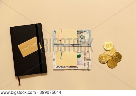 Business Concept Items On The Table Gold Bitcoins, Dollars, Diary, Gold Card, On A Beige Background.