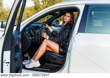 Young Brunette Girl With Long Hair In A Leather Black Jacket And A Skirt With Beautiful Legs Driving