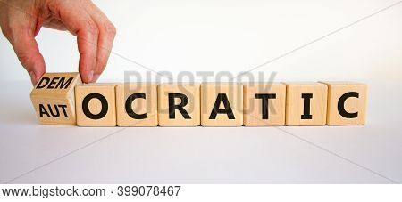 Democratic Or Autocratic Symbol. Male Hand Turns A Cube And Changes The Word 'autocratic' To 'democr