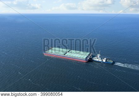 Tugboat Pulling Barge With Cargo By Water,  Aerial View